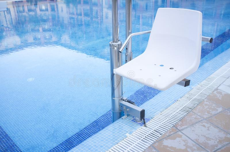 Swimming pool lift for disabled people access to the pool. Holidays resort background stock photography