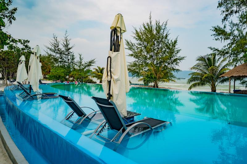 Swimming pool luxury holiday hotel, amazing view. Relax near pool with handrail, sunbeds, sun loungers and parasols waiting for stock photos