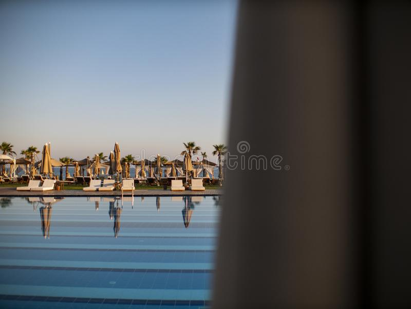 Swimming pool of luxury holiday hotel, amazing view. Relax near pool with handrail, sunbeds, sun loungers and parasols waiting for royalty free stock images
