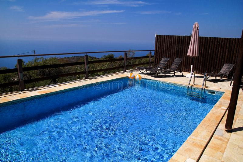 Swimming pool of luxury holiday villa, amazing nature view landscape sea. Relax near swimming pool with handrail, deck chairs. royalty free stock image
