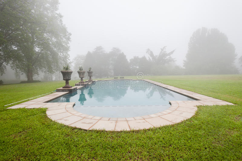 Swimming Pool Mist Landscape. Morning cloud mist over swimming pool home grass landscape royalty free stock photography