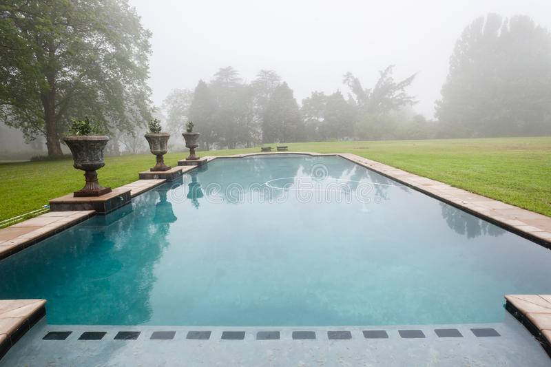 Swimming Pool Mist Landscape. Morning cloud mist over swimming pool home grass landscape royalty free stock images