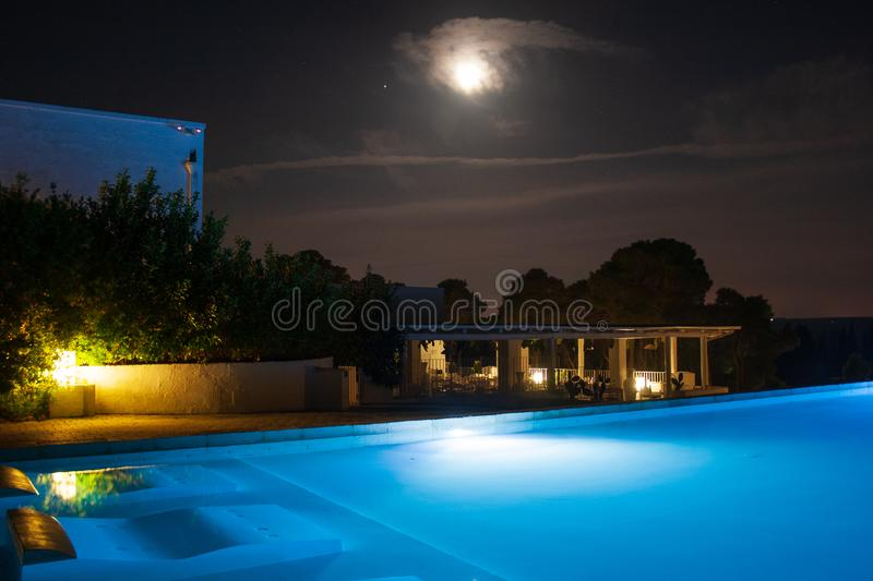 Swimming pool at night with moon. Swimming pool in beautiful luxury resort into the nature with no people, near Laghi Alimini, Lecce, Salento, Puglia, South royalty free stock photo