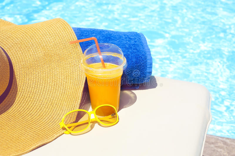 Swimming pool, orange juice, beach towel, sunglasses. On sun bed. Summer vacation concept royalty free stock photography