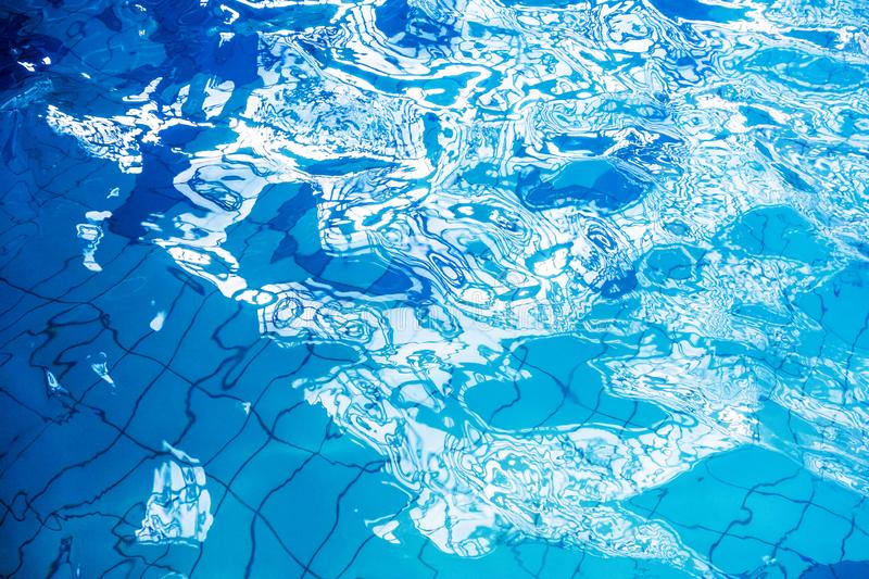 Swimming Pool Rippled Water. Blue swimming pool rippled water detail with sunny reflection stock photos