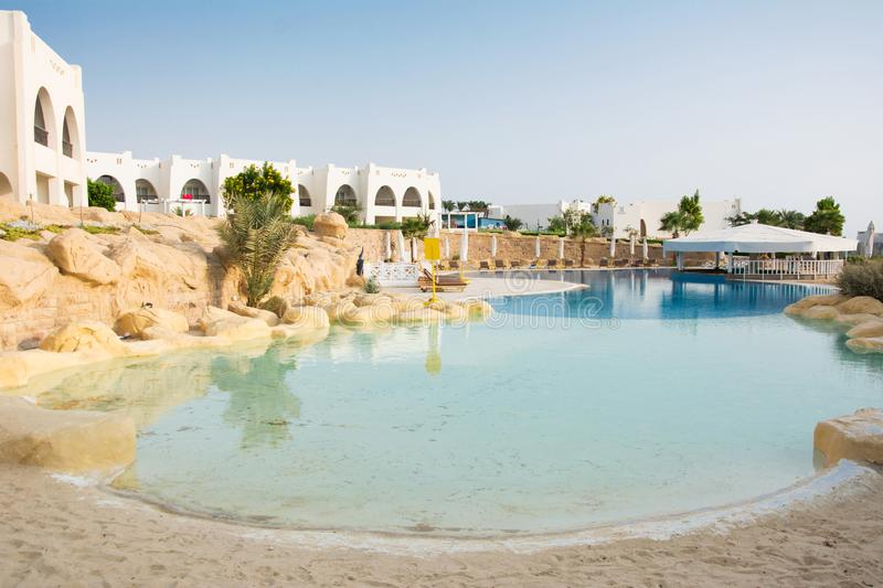 Swimming pool with sand entrance in Egypt. Empty sun-loungers ne stock image