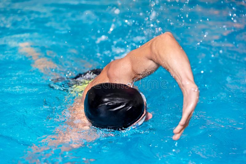 Swimming pool sport crawl swimmer. Man doing freestyle stroke technique in water pool lane training for competition. royalty free stock photos
