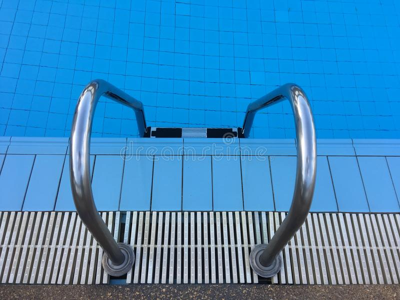 Swimming pool with stair and blue water royalty free stock photos