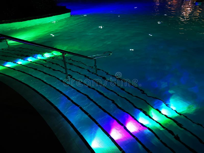 Swimming pool staircase colorful illuminated night royalty free stock images