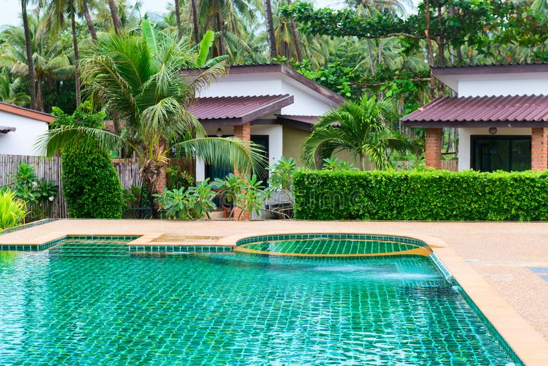 Swimming pool in a tropical hotel with palms and bungalows. Swimming pool in a tropical hotel with green palms and bungalows on background stock image