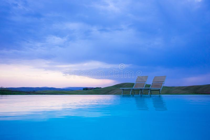Swimming pool with two sun beds in evening light by sunset. Travel concept stock photos