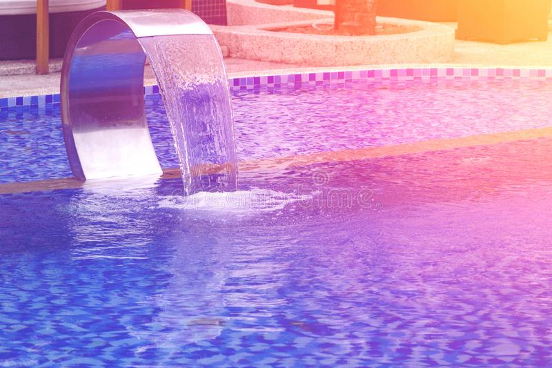 Swimming pool with waterfall jet stock images