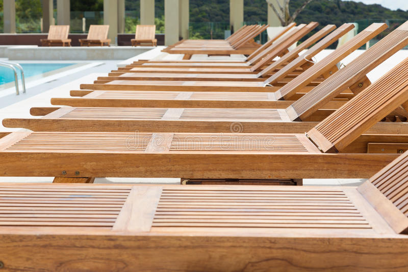 Swimming pool with wooden sunbeds. stock images