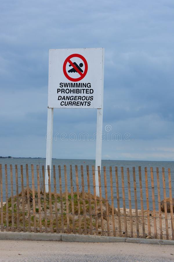 Swimming Prohibited Dangerous Currents warning sign at ocean beach shoreline. Large Swimming Prohibited Dangerous Currents warning sign at an ocean beach stock photo