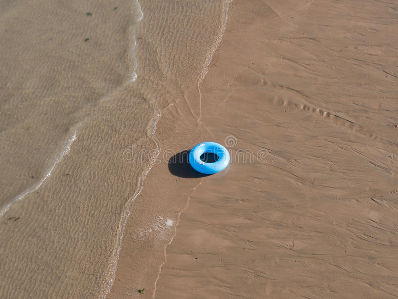 Swimming ring on the beach royalty free stock image