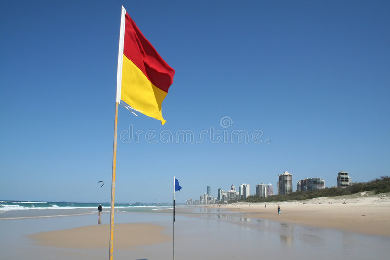Swimming Safety Flags Gold Coast. Swimming safety flags on the Gold Coast Northern beach looking towards Surfers Paradise royalty free stock photo