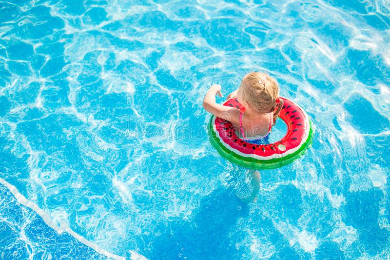 Swimming, summer vacation - lovely smiling girl playing in blue water with lifebuoy-watermelon stock photos