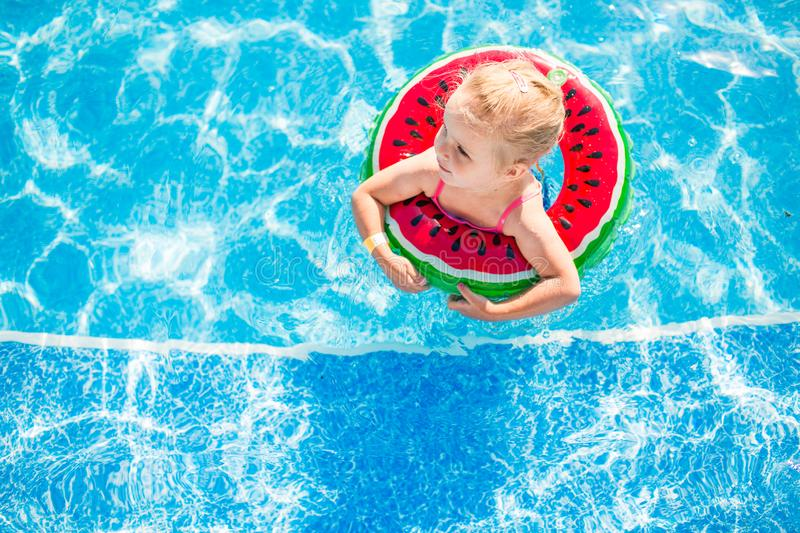Swimming, summer vacation - lovely smiling girl playing in blue water with lifebuoy-watermelon stock photo