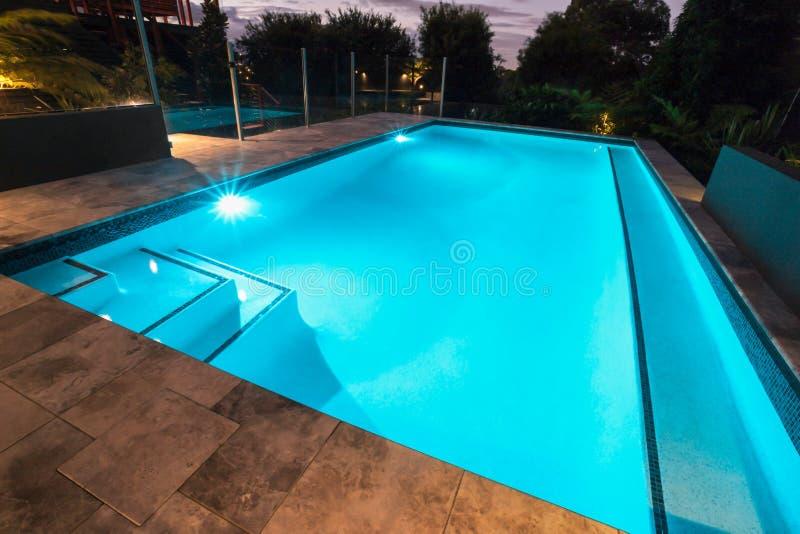 Swimmingpool des blauen Wassers mit Blinklichtern mit Bodenfliesen stockfotos