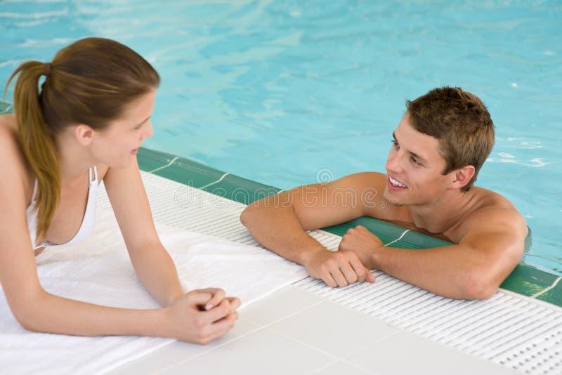 Swimmingpool - glückliche Paare plaudern auf Poolside stockbilder