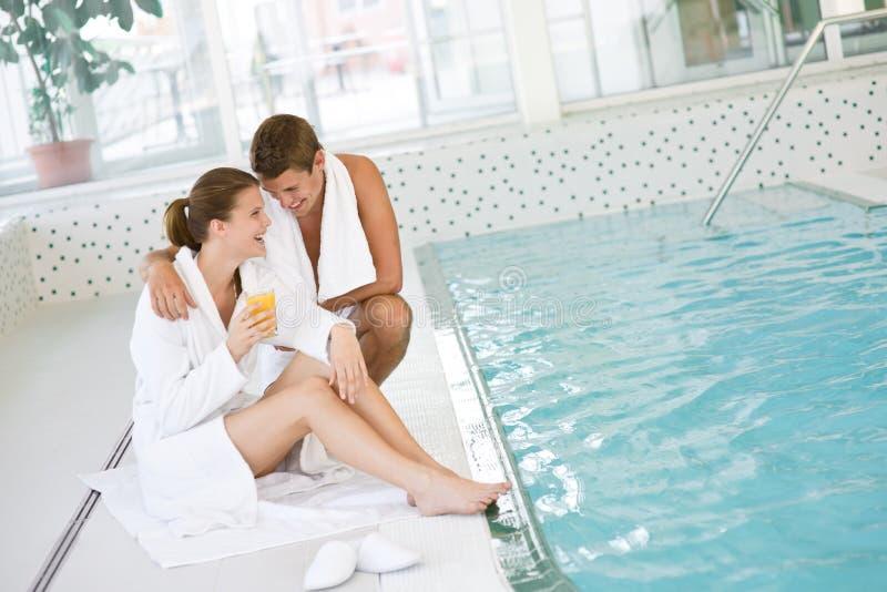 Swimmingpool - junge glückliche Paare entspannen sich lizenzfreie stockfotos