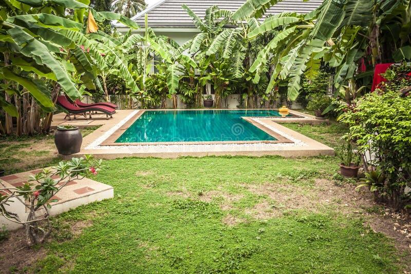 Swimmingpool am privaten tropischen Landhaushinterhof unter tropischem formalem Garten mit Palmen und Türkis wässern lizenzfreies stockfoto