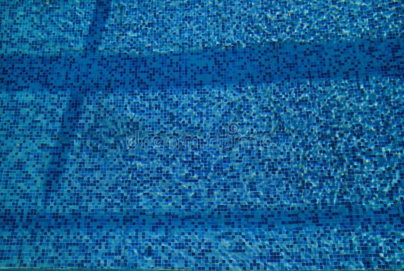 Swimmingpool-Unterseitenätzmittel plätschern und fließen mit Wellenhintergrund Oberfläche des blauen Swimmingpools, Hintergrund d lizenzfreies stockbild