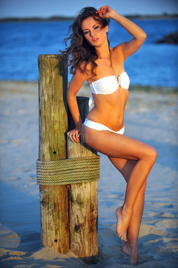 Swimsuit model with perfect fit body posing on the beach stock images