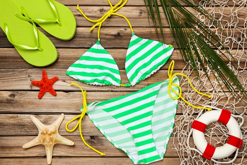 Swimsuit with palm leaf and flip flops stock image