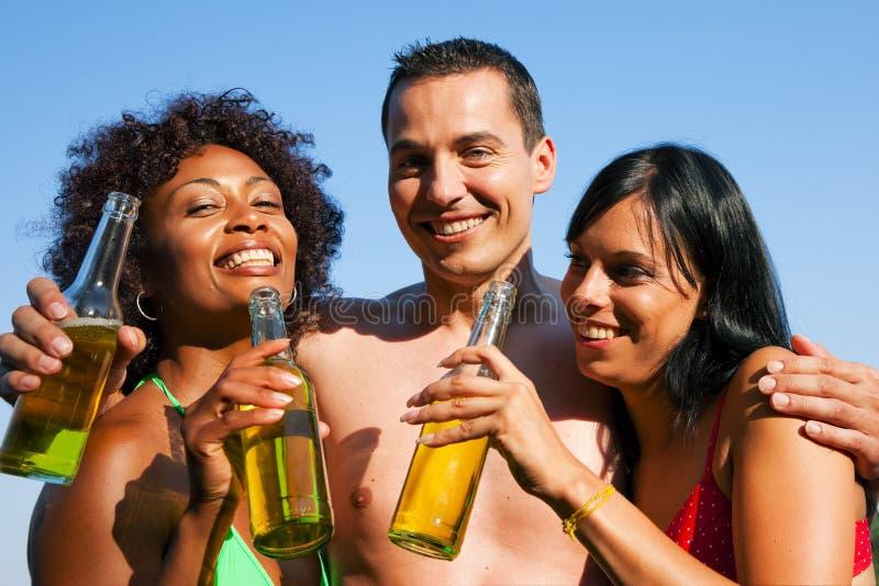 swimwear группы друзей пива выпивая стоковые изображения