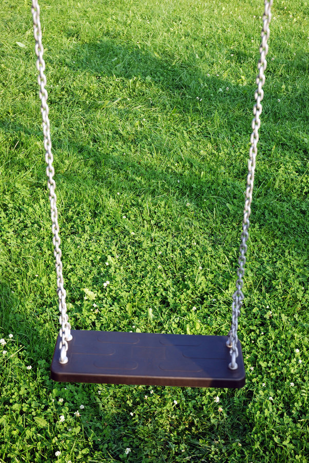 Swing 1. Empty hanging swing in the garden royalty free stock image
