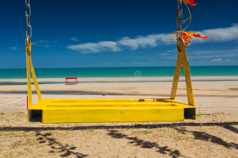 Swing on the beach. The swing of the yellow paint on the beach looks very beautiful royalty free stock photo