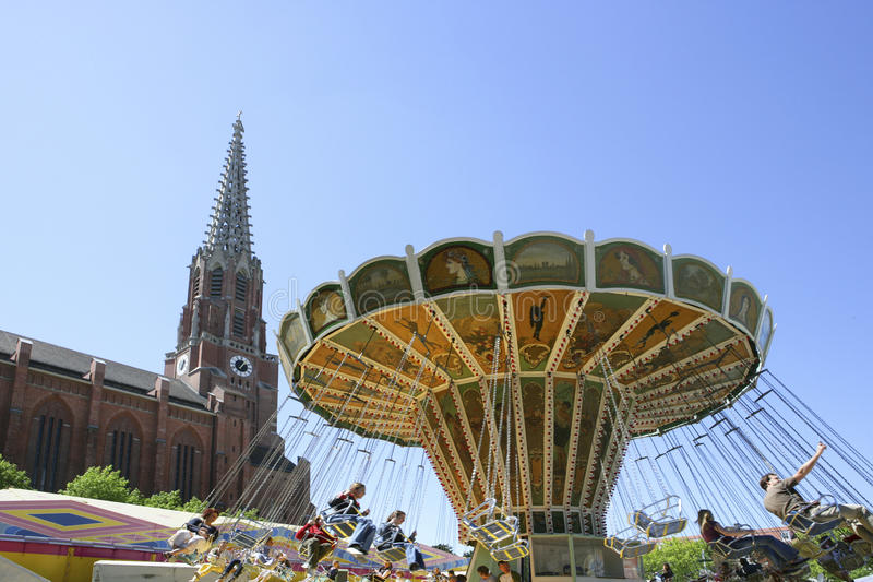 Swing Carousel at the Auer Dult Traditional Market in Munich. Chair-O-Plane in Front of Mariahilf Church at the Auer Dult, traditional market in Munich, Bavaria royalty free stock photos