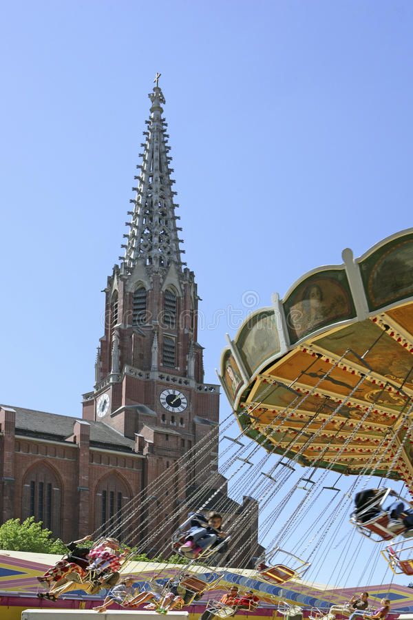 Swing Carousel at the Auer Dult Traditional Market in Munich. Chair-O-Plane in Front of Mariahilf Church at the Auer Dult, traditional market in Munich, Bavaria stock photo