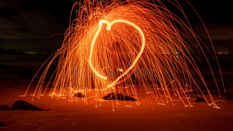 Swing fire Swirl steel wool light photography with reflex in the water long exposure speed motion style.  stock photo