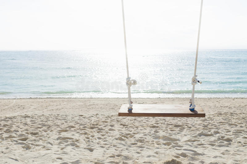 Swing in front of the ocean, nusa lembogan, Bali, Indonesia. Swing at the beach with sunlighted water in front of the ocean, nusa lembogan, Bali, Indonesia stock photo