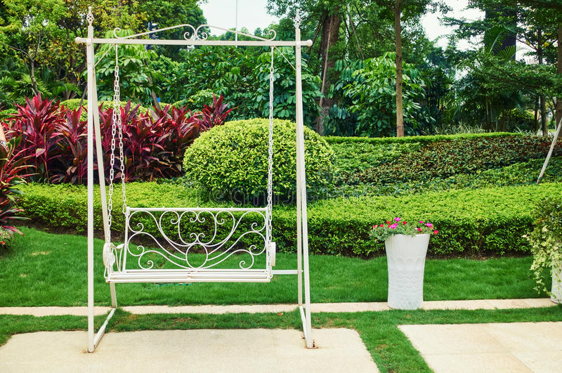 Swing in backyard garden. Empty swing in backyard flower garden royalty free stock photos