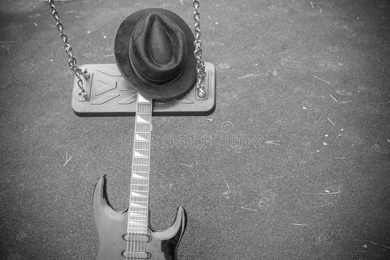 Swing music, a concept. Electric guitar on a swing, a music genre concept stock photo