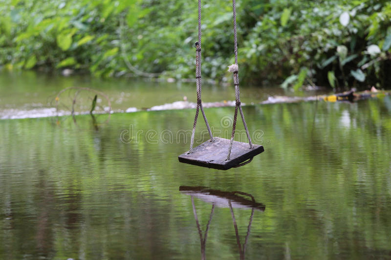 Swing over the water. Wooden swing over the water and its reflection stock images