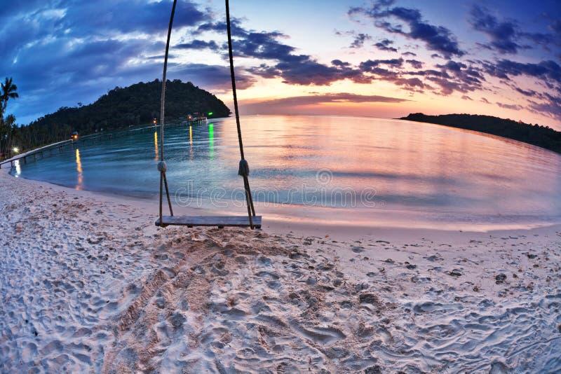 Swing på solnedgång på stranden royaltyfri fotografi