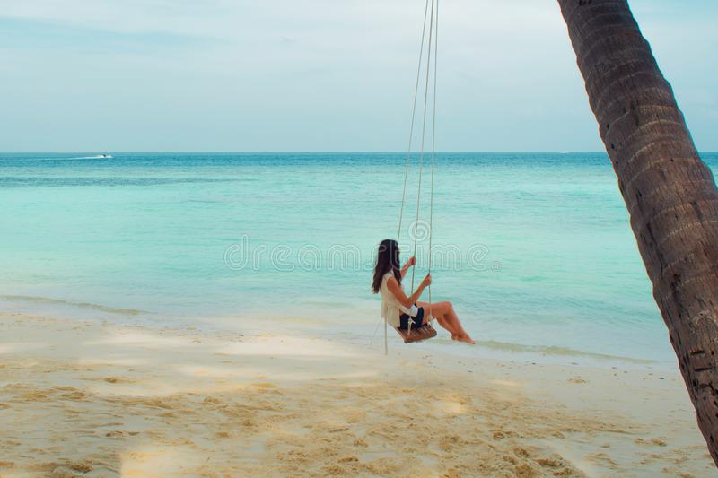 Swing on a palm tree. Beautiful island landscape with relaxing girl on a swing. Tropical resort stock photos