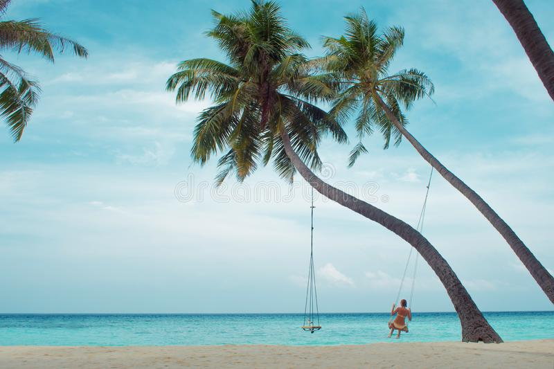 Swing on a palm tree. Beautiful island landscape with relaxing girl on a swing. Tropical resort royalty free stock image