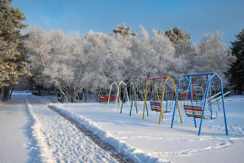 Swing at the playground covered with snow in winter time. royalty free stock images