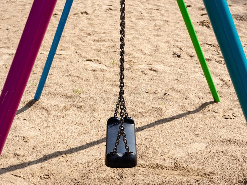 Swing on sandy children`s playground with black plastic seat hanging on chains. royalty free stock photos