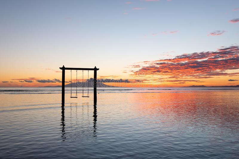 Swing on seashore during the sunrise. Sky and reflections on the water in the summer. Nusa Penida, Bali, Indonesia. Travel - image stock photography