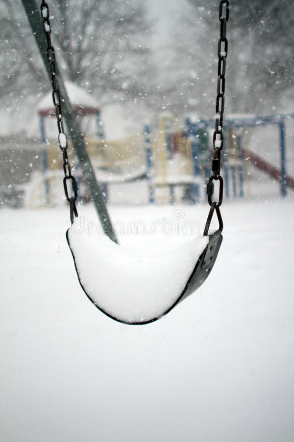 Swing in a snow storm. Playground during a snow storm royalty free stock image