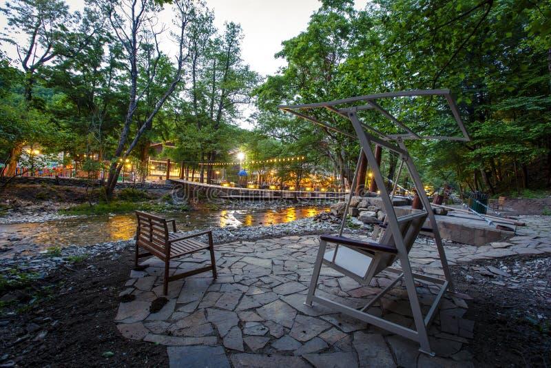 Swing and vila place on the Bank of a Bergflod royaltyfri foto