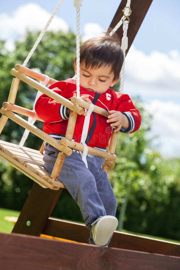 Swinging. Adorable kid swinging outdoors on the sunny day stock images