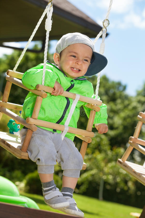 Swinging baby. Adorable happy kid swinging outdoors stock images