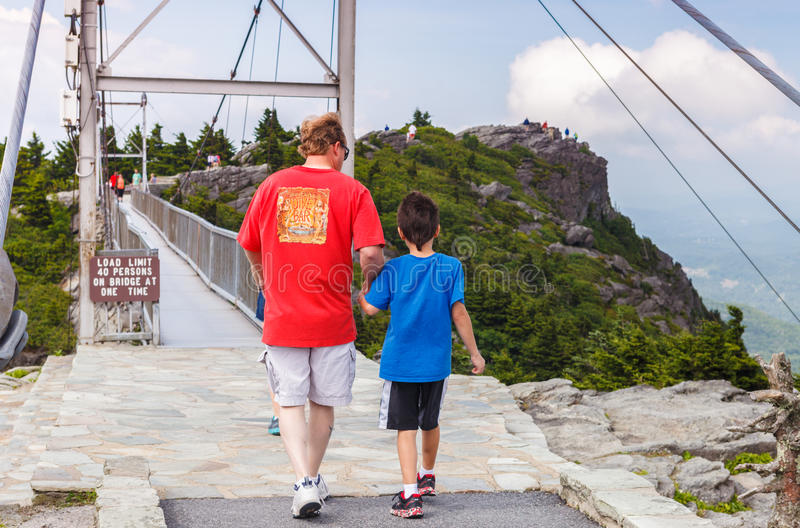 Swinging Bridge -Man with Boy Conquering Fear. Man holds the hand of a young boy to help him conquer his fear of crossing the mile-high swinging bridge at stock image